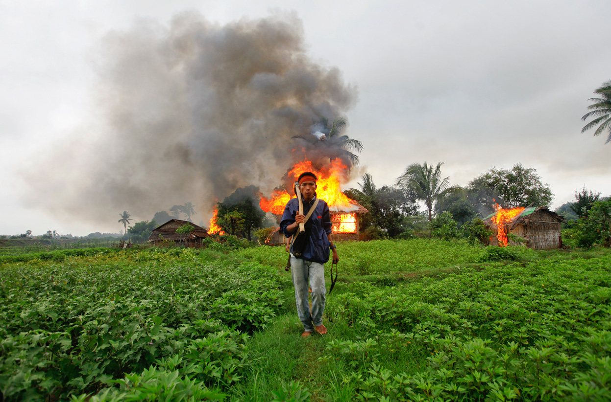 A resident of Rakhine State walks past burning homes during anti-Rohingya violence in Sittwe during summer 201