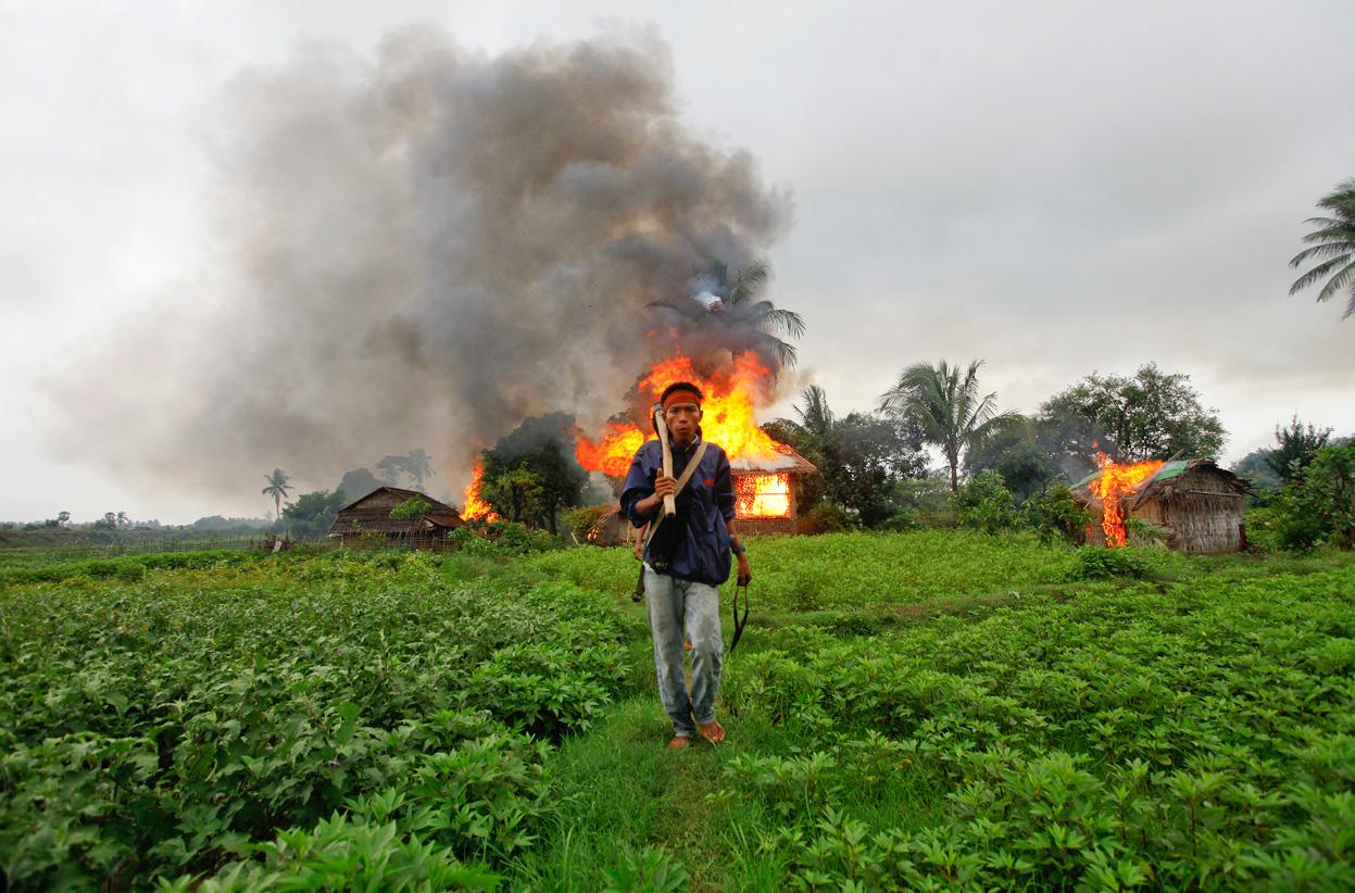 A resident of Rakhine State walks past burning homes during anti-Rohingya violence in Sittwe during summer 2012