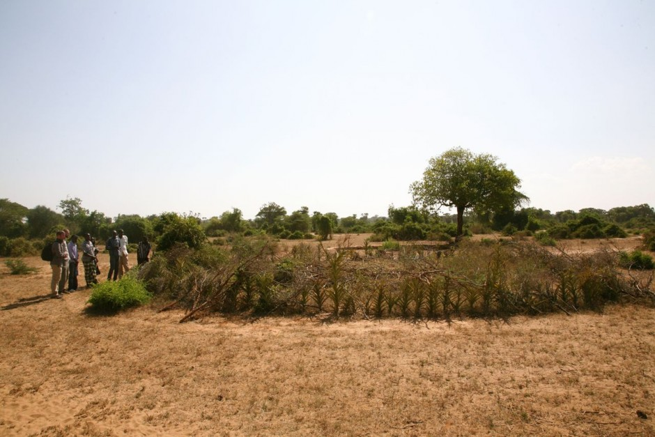 Sentinel Project team members pay their respects at a mass grave on the outskirts of Kipao, within which lie the remains of 5 women, 16 children, and 10 men.